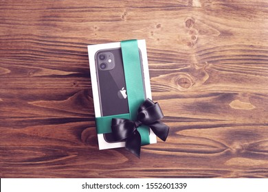 Riga / Latvia - November 7 2019: a box of new Apple iphone 11 with green ribbon and black bow on wooden textured background. Top view, flat lay, copy space. Gift concept.