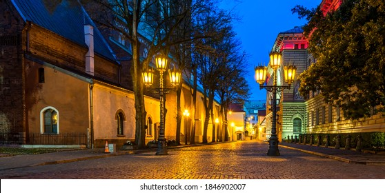 Riga, Latvia - October 01, 2019: Autumnal night in center of old Riga with nocturnal view on decorative street lamps, rubble square, wall of medieval church and old buildings of 19-th century
