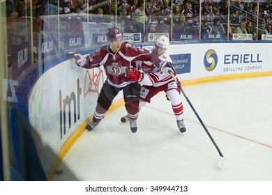 RIGA, LATVIA - OCTOBER 1: Viktor Baldayev (14) tries to stop Roberts Locans (12) reach the puck at the boards  in KHL game between Dinamo Riga and Spartak played on OCTOBER 1, 2015 in Arena Riga