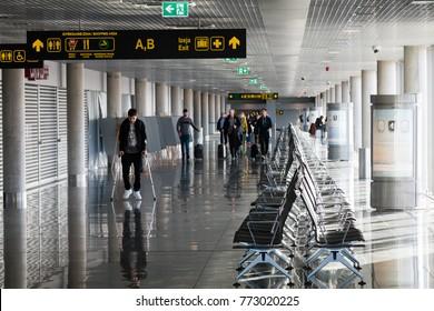 Riga, Latvia - October 13th 2017:Passengers walking though the departure hall waiting area at Riga International airport.