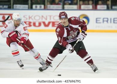RIGA, LATVIA - OCTOBER 29: Alexei Dostoinov (62) tries to stop Lauris Darzins (10) in KHL game between Dinamo Riga and Avtomobilist Jekaterinburga played on OCTOBER 29, 2015 in Arena Riga