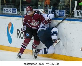 RIGA, LATVIA - OCTOBER 3: Aleksandrs Jerofejevs (23) checks Alexander Osipov (47) into the boards in the KHL game between Dinamo Riga and Dynamo Moscow, played on October 3, 2016 in Arena Riga