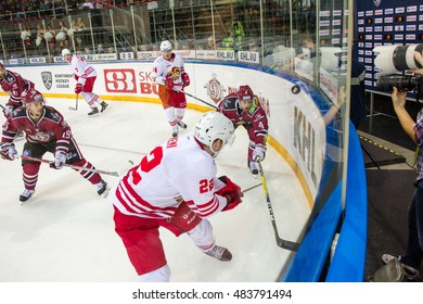 RIGA, LATVIA - SEPTEMBER 13:  Mika Niemi (22) and Justin Shugg (4) reach for the puck at the boards in the KHL game between Dinamo Riga and Jokerit, played on September 13, 2016 in Arena Riga