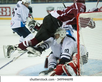 RIGA, LATVIA - SEPTEMBER 23:  Miks Indrasis (70) crashes into goalie Danny Taylor (30)  in KHL game between Dinamo Riga and Medvescak Zagreb played on SEPTEMBER 23, 2015 in Arena Riga