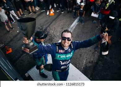 Riga, LV, Bikernieki Raceway - JUN 29, 2018: Drift Challenge Battle of Nations 2018 Formula D driver Matt Field at the podium with cup and champagne