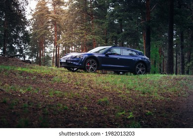 Riga, LV - MAY 28, 2021: Porsche Taycan Cross Turismo at the wood