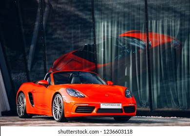Riga, LV - SEP 27, 2018: Porsche 718 Boxster near modern building with reflection at glass