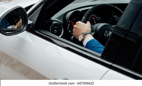 Riga, March 17, 2017 - White Alfa Romeo Giulia Quadrifoglio is driven by a young man in blue suit with golden wristwatch.