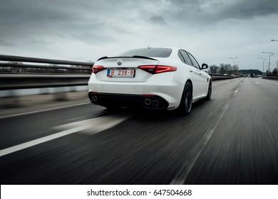 Riga, March 17, 2017 - White Alfa Romeo Giulia Quadrifoglio is driven at high speed on streets of Riga. Some motion blur visible.