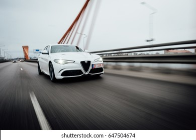 Riga, March 17, 2017 - White Alfa Romeo Giulia Quadrifoglio is driven at high speed on streets of Riga.