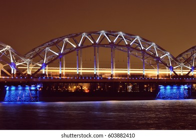 Riga Railway Bridge at night and bright yellow line of a passing train, Latvia