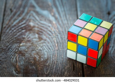 RIGA - SEPTEMBER 16, 2016: Rubik's Cube on the Dark Wooden Background, Free Space for Text