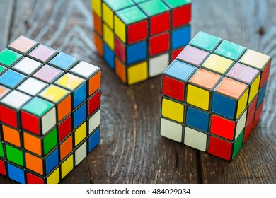 RIGA - SEPTEMBER 16, 2016: Three Rubik's Cubes on the Dark Wooden Background