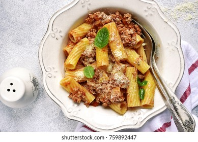 Rigatoni with meat sauce in a vintage bowl over light slate,stone or concrete background.Top view.