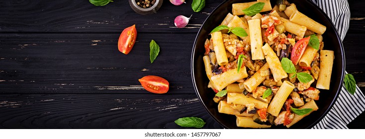 Rigatoni pasta with chicken meat, eggplant in tomato sauce in bowl. Italian cuisine. Top view. Banner