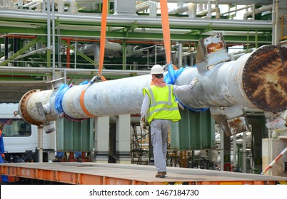 Rigger construction worker holding control a primary transfer line of heat exchanger which its connecting to the load while crane is lifting construction site or chemical plant.