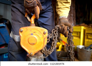 Rigger high risk worker wearing heavy duty glove, doing checking inspection a  heavy duty 3 tones lifting chains block prior used on construction mine site Perth city, Australia