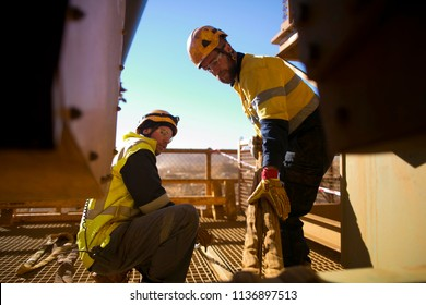 Riggers wearing a fall safety protection helmet are working on final safety check of three tone crane lifting sling inspection before commencing the task on construction site Perth, Australia