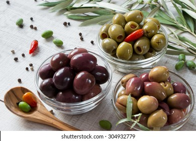 Right 3 bowls with kind of olives green olives, black olives, green olives stuffed with pepper framed by olive tree branches and scattered peppercorns . 3 types of olives. Horizontal shot.Daylight.