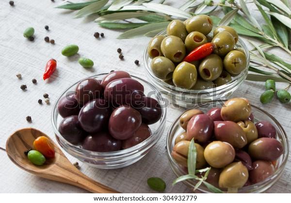 Pravá 3 mísy s druhy oliv zelené olivy, černé olivy, zelené olivy plněné pepřem orámované olivovníky a rozptýlené pepře. 3 druhy oliv. Horizontální výstřel.Denní světlo.