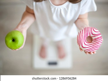 Right choice. Little girl holding green apple in one hand and donut in another. Kid trying to make decision between healthy and unhealthy food. Dieting, healthy eating, lifestyle. Obesity. Top View