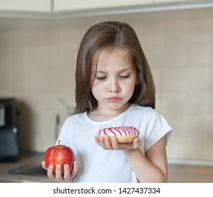 Right choice. Little sad girl holding in hands apple and high-calorie donut. Unhappy child in the kitchen. Kid trying to make decision between healthy and unhealthy food. Dieting, eating, lifestyle