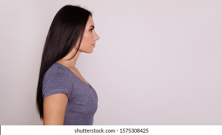 Right direction. Close-up photo of a young lovely woman with long dark hair, posing in profile, and looking towards the direction she is facing.