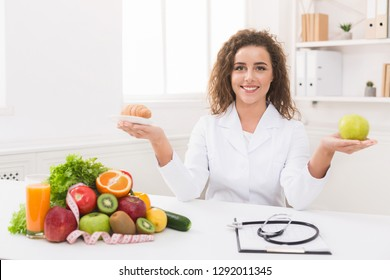 Right eating nutrition concept. Female nutritionist holding fruit and croissant, comparing junk and healthy food, panorama, copy space