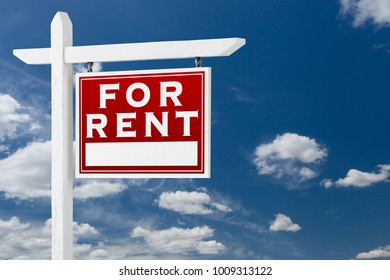 Right Facing For Rent Real Estate Sign Over Blue Sky and Clouds With Room For Your Text.