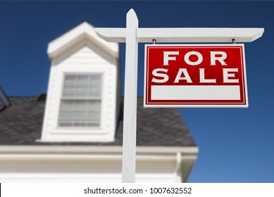 Right Facing For Sale Real Estate Sign In Front of House and Deep Blue Sky.