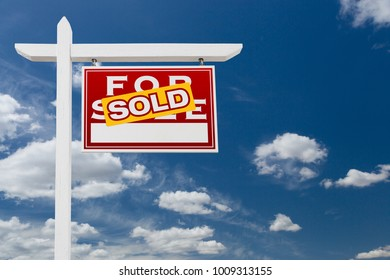 Right Facing Sold For Sale Real Estate Sign Over Blue Sky and Clouds With Room For Your Text.