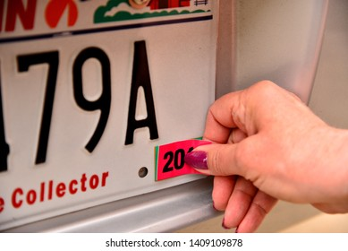 Right female hand applying annual registration year sticker with thumb and forefinger.