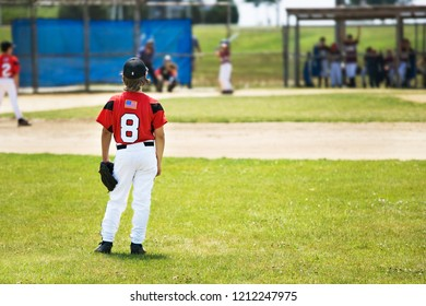 right fielder looking into the infield at a little league baseball game.