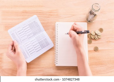 Right hand of asian woman are recording expenses in a notebook and left hand holding account book,plan and financial concept.