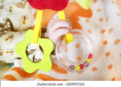 Right hand baby holding a rattles of different shapes in warm colors.