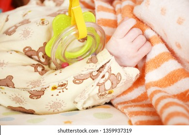 Right hand baby is next to thea rattles of different shapes in warm colors.