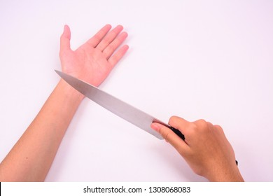 A right hand holding a stainless steel knife on her left wrist in cutting gesture. Isolated on white background.