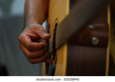 right hand of the man play guitar