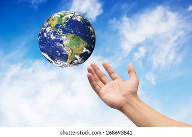 Right hand palm gesture with earth on blue sky backgrounds. Elements of this image furnished by NASA