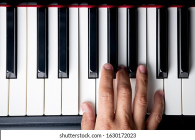 right hand playing a F Major  chord on the piano