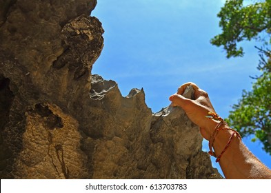 RIGHT HAND ROCK CLIMBER CLIMBING AND GRASP HANDHOLD ON NATURAL CLIFF WITH BLUE SKY CLOUDS AND GREEN TREES BACKGROUND