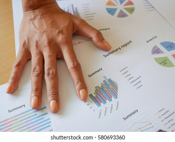 Right hand of sales manager place on business reports.Very serious situation.