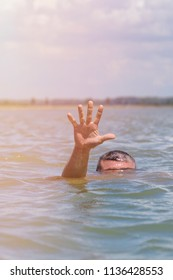 right man's hand gives a signal for help out of the water, a man drowns in the sea on a summer day
