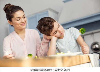 Right nutrition. Attractive inspired dark-haired young mom smiling and having healthy breakfast with her son and the boy looking seriously at the vegetable on his fork