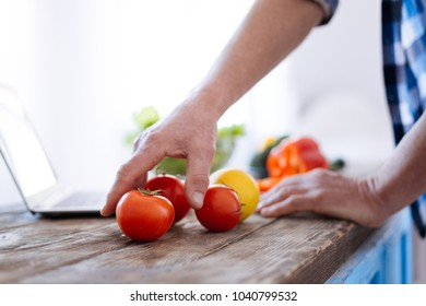 Right nutrition. Close up of attractive handsome male hands reaching for tomato for trying biohacking diet and cooking lunch