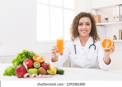 Right nutrition and slimming concept. Friendly woman nutritionist with orange juice and orange at office, panorama, copy space