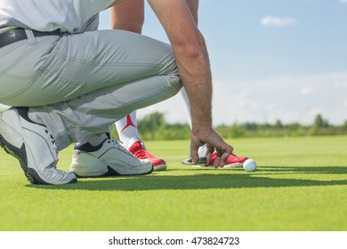 Right placement. Cropped shot of a male golfer placing the ball and tee in the ground in front of his female partner player