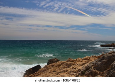 Right side view of Castell beach with rainbow clouds on background, one of the most amazing virgin spots of la Costa Brava seaside, Palamós, Girona, Catalonia, Spain.