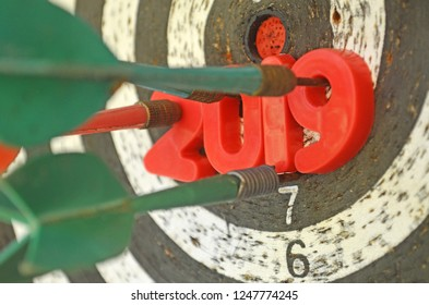 Right in target. 2019 achievement. New year goal and resolution. Darts board with plastic numbers struck by arrow.