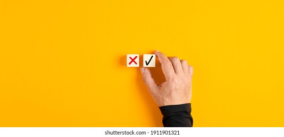 Right and wrong icons on wooden cubes with male hand choosing the right icon on yellow background. Approving, voting or right decision concept.